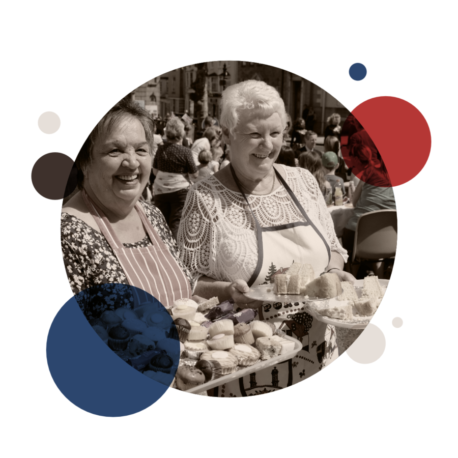 Photo of two smiling older ladies holding trays of cupcakes to give out during the Queens Jubilee celebrations in Penryn town centre